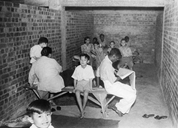 The Japanese Campaign and Victory: 8 December 1941 - 15 February 1942: Civilians in a Singapore air raid shelter during a Japanese bombing raid. © IWM (KF 102)