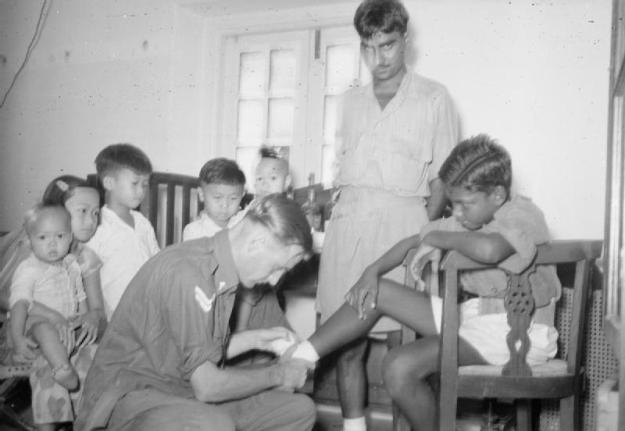Royal Air Force Regiment medical orderly, Corporal L Cooper, takes a clinic for Chinese, Indian and Malay residents of Penang Hill where he is based with a small garrison detachment of one officer and 30 men. © IWM (CF 1021)