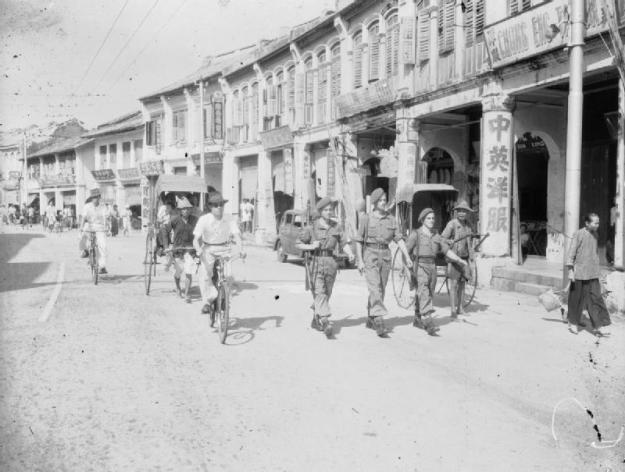 Three members of the Royal Air Force Regiment on foot patrol in Georgetown the capital of Penang, Malaya. © IWM (CI 1665)
