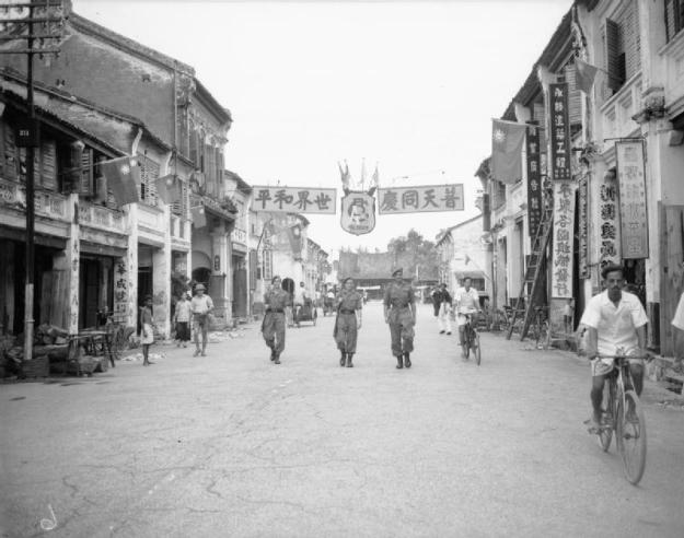 Men of the Royal Air Force Regiment on foot patrol in Georgetown, Penang. They are passing beneath a Chinese banner that celebrates the victory over Japan. © IWM (CI