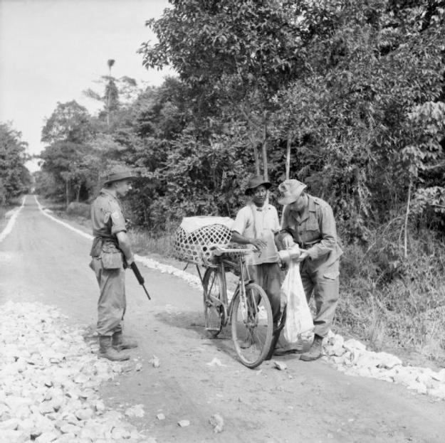 Sergeant William Goldie of the 1st Battalion The Loyal (North Lancashire) Regiment searches a Malay cyclist on a road near Ipoh for any supplies or material he may be smuggling through to the communist guerillas. © IWM (D 88057)