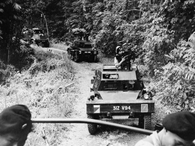 A convoy of vehicles of the Malayan Armoured Corps, led by a Ferret armoured car, move along a road through the jungle. © IWM (K 14063)