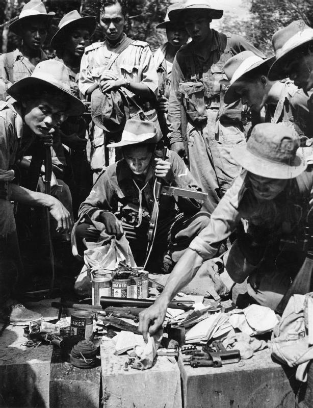 Members of the Malay Regiment inspect equipment, supplies and documents captured in a raid on a communist terrorist jungle camp.