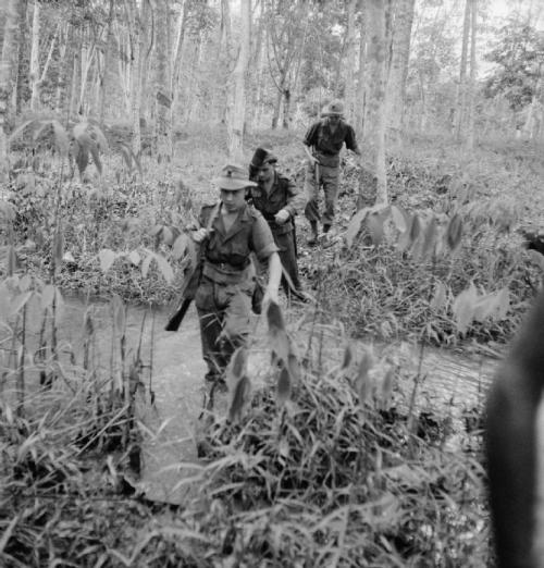 Soldiers of the 1st Battalion, the Suffolk Regiment (possibly C Company) cross a stream in the middle of a jungle swamp whilst on a patrol during the Malayan Emergency. © IWM (BF 10373)