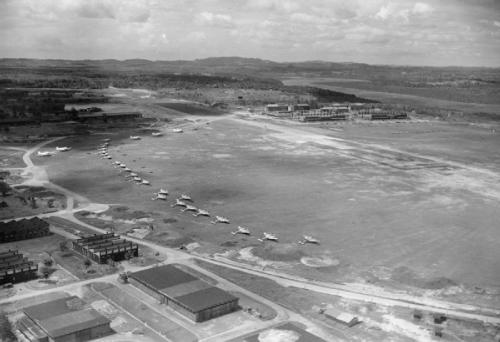 An aerial view of Seletar airfield, Singapore, with Royal Air Force Mosquito and Dakota aircraft parked up. © IWM (CI 1735)