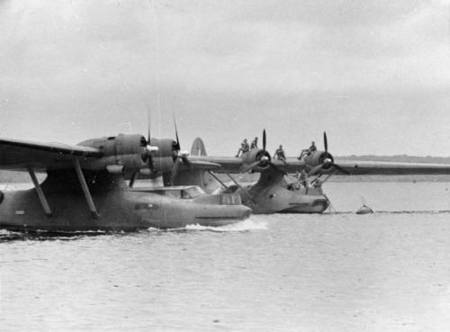 A Consolidated Catalina Mark I of No. 205 Squadron RAF taxies past another aircraft of the Squadron moored in the Strait of Johore off Seletar, Singapore. © IWM (K 1117)