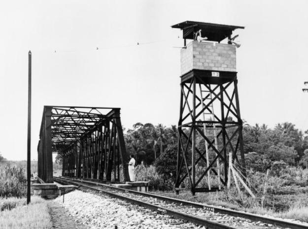 A watch tower manned by the Malayan Home Guard protects a railway bridge from sabotage by Communist guerrillas. © IWM (K 14430)